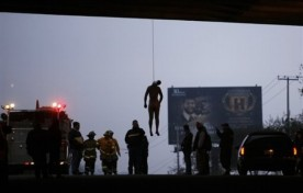 ** ADDS INFORMATION FROM AUTHORITIES REGARDING IDENTITY OF VICTIM ** The body of an unidentified man hangs from his neck under a bridge on the old Rosarito highway as authorities stand by in Tijuana, Mexico, Friday, Oct. 9, 2009. Authorities found the dead man beaten, naked and castrated, and have not identified him but believe he is Rogelio Sanchez, a Baja California state government official who went missing this week. No suspects were named. The homicide is characteristic of Mexico's brutal drug gangs, which often dump mutilated victims in public places. (AP Photo/Guillermo Arias)